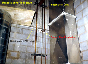 "Duct (flow) - Fire-resistance rated mechanical shaft with HVAC sheet metal ducting and copper piping, as well as ""HOW"" (Head-Of-Wall) joint between top of concrete block wall and underside of concrete slab, firestopped with ceramic fibre-based firestop caulking on top of rockwool."