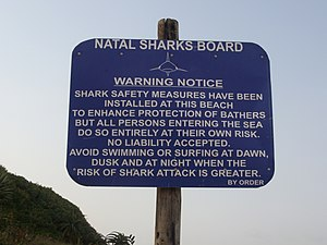 "A photograph of a rectangular sign attached to a wooden post. White text on a blue background reads ""Natal sharks board. Warning notice. Shark safety measures have been installed at this beach to enhance protection of bathers but all persons entering the sea do so entirely at their own risk. No liability accepted. Avoid swimming or surfing at dawn, dusk and at night when the risk of shark attack is greater. By order."""