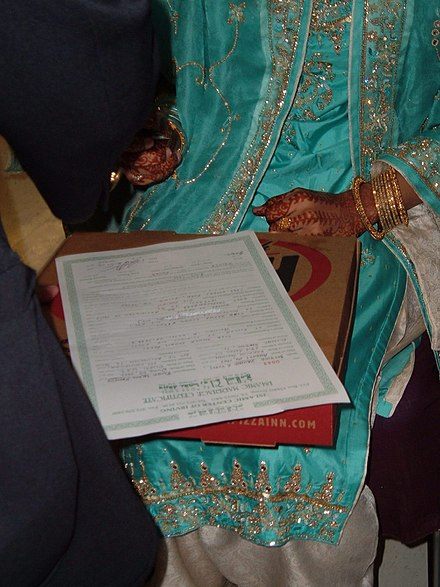 A Muslim bride of Pakistan origin signing the nikkah nama or marriage certificate. Signing the Nikah.jpg
