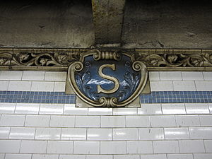 "Spring Street (IRT Lexington Avenue Line) - Small ""S"" cartouches, Atlantic Terra Cotta (1904)"