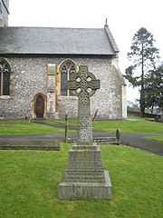 Stone Celtic cross in front of a church