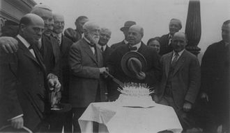 Nicholas Longworth - Speaker Longworth shakes hands with North Carolina Representative Charles Manly Stedman and presents a congressional birthday cake with eighty-five candles along with fellow congressmen in front of the United States Capitol, January 30, 1926.