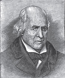 A man, bald on top with long white hair in the back, wearing a black jacket and tie and white shirt