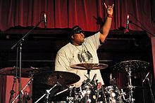 El baterista de la banda Suicidal Tendencies, Eric Moore, se muestra detrás de su batería.  Se levanta una mano con el dedo índice y el meñique extendido.