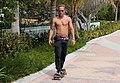 Tattoeed skateboarder riding on beach shirtless.jpg