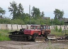 Двигатели и кабина трелёвочного трактора ТДТ-55 расположены спереди.  За ними платформа для трелёвки леса.