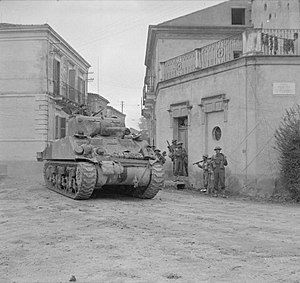 Warwickshire Yeomanry - A Sherman tank of 'B' Squadron, Warwickshire Yeomanry, passing Indian infantry in Frisa, Italy, 14 December 1943.