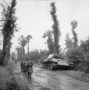 56th Infantry Brigade (United Kingdom) - Infantrymen of the 2nd Battalion, Essex Regiment file past a knocked out German Panther tank on a road near Tilly-sur-Seulles, France, 19 June 1944.