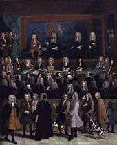 A rectangle picture of a courtroom.  Dozens of men in a courtroom in 1750s era court suits and wigs.  A blue wall at the back contains a coat of arms.  On a raised stage at the back are four men.  Several onlookers, some with dogs and children, pass by on a sidewalk looking in on the court proceedings.
