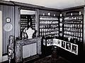 The corner of a room with decorated pharmacy jars on shelves Wellcome V0029791.jpg
