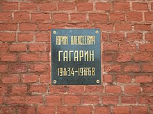 Plaque on a brick wall with inscription: Юрий Алексеевич Гагарин, 1934-03-09–1968-03-27