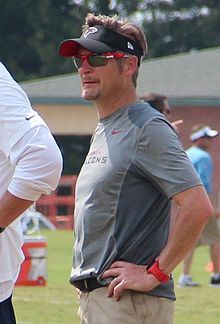 Candid waist-up photograph of Dimitroff wearing a grey t-shirt and black visor both bearing Atlanta Falcons logos and standing on a football practice field with arms akimbo