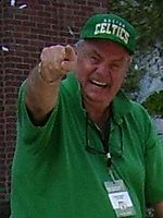 "A man wearing a green t-shirt and a green cap with a word ""CELTICS"" are pointing his hand towards the camera."