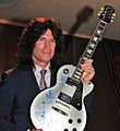 Tommy Thayer without KISS makeup, holding up autographed guitar, 2013.jpg