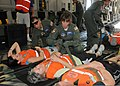 U.S. Air Force Capt. Rita O'Brian, center, and Tech. Sgt. Joseph Carolan, center left, both with the 109th Aeromedical Evacuation Squadron, secure mock victims to stretchers during exercise Golden Eagle III 130601-Z-VX101-013.jpg