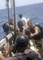U.S. Navy and Marine Corps visit, board, search and seizure team members stationed aboard the guided missile cruiser USS San Jacinto (CG 56) stand guard over suspected pirates on board a dhow as they travel 100527-N-EF447-196.jpg