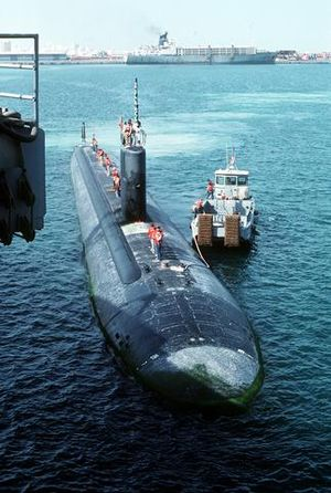 The USS Topeka (SSN-754) prepares to dock with the assistance of a tugboat.