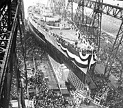 A large warship, still missing most of its superstructure, sits in a dry dock, awaiting its launch. The ship is draped in a large banner and surrounded by crowds of spectators; a huge gantry towers over the ship.