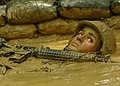 US Navy 050817-N-1261P-169 U.S. Navy Construction Mechanic 3rd Class Peter Welch back crawls through mud-filled trenches as part of an obstacle course.jpg