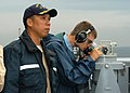 US Navy 060901-N-2716P-027 USS Gary (FFG 51) Commanding Officer, Cmdr. Joseph Deleon, looks out from the bridge wing as Quartermaster Seaman Michael Lind takes a bearing reading.jpg