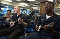 US Navy 060902-N-9851B-011 Culinary Specialist Seaman Damien McCullough, left and Lt J.G. Levy-Minzie play an electric guitar video game on the mess deck of aboard the guided missile destroyer USS Hopper (DDG 70).jpg