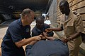 US Navy 071115-N-0193M-204 Lt. Raul Ona Micha, from Equatorial Guinea, learns how to safely place handcuffs on a suspect with the help of Coast Guard Chief Boatswain's Mate Anthony Cirillo and fellow classmate Lt. Jean Pierre T.jpg