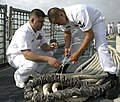 US Navy 090504-N-7090S-334 Chief Boatswain's Mate Fransisco Valdovinos, teaches Engineman 2nd Class Janis Francis how to tie a square knot on the flight deck of the littoral combat ship USS Freedom (LCS 1).jpg