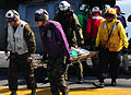 US Navy 100120-N-7508R-213 Fight deck crew members aboard USS Bataan (LHD 5) carry a Haitian woman to the ship's flight deck triage for immediate medical treatment.jpg