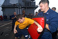 US Navy 110806-N-DU438-658 Interior Communications Electrician 2nd Class Aaron Aguilera, left, punches a bag held by Electronics Technician 3rd Cla.jpg
