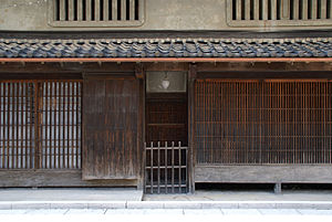 Machiya - Facade of a shop in the historic Matsuyama merchant quarter, Uda city, Nara prefecture; example of machiya design. Kōshi latticework on the ground floor; earthwork walls on the second story with mushikomado windows. Clay roof tiles.