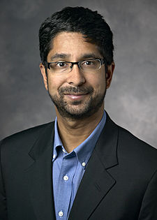 A portrait of Vijay Pande, looking straight ahead. His ethnicity is Indian. He has medium-length black hair, black-rim glasses, and a short mustache and beard. He is wearing a blue polo shirt under a black suit coat.