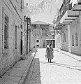 Vrouw lopend over straat met gevogelte in haar beide handen, Bestanddeelnr 255-2480.jpg