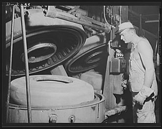 Vulcanization - Worker placing tire in a mold before vulcanization.