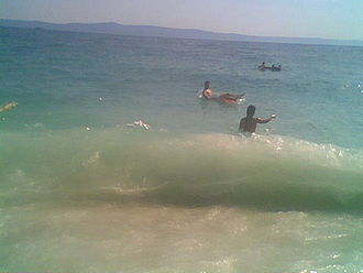 Gravity wave - Surface gravity wave, breaking on an ocean beach.