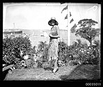 Woman with clutch bag and hat posing for the camera with a regatta in the background, 1920-1935 (7513027354).jpg