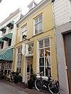 foto van Huis met lijstgevel met versierde ingangspartij met gesneden bovenlicht en deur