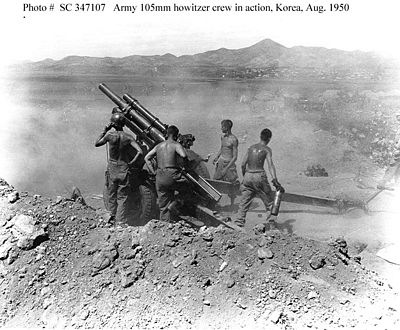 Gun crew of the 64th Field Artillery Battalion, 25th Infantry Division, fire a 105mm howitzer on North Korean positions near Uirson, South Korea, 27 August 1950.