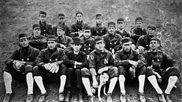 "A black and white photograph of seventeen men sitting in three rows on the ground. Most are wearing dark coats with high white socks, but two are wearing dark baseball uniforms with a white ""N"" on the chests; some are wearing fielding gloves, and one is petting a dog."