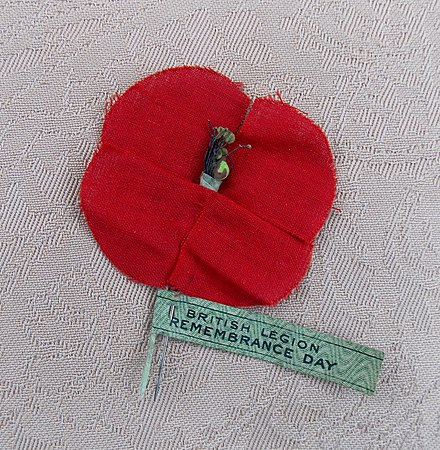 "1921 British Remembrance Poppy. Cotton and silk poppies were made by Madame Guerin's widows & orphans in the devastated areas of France. Madame Guerin was ""The Poppy Lady from France"" and the ""Originator of the Poppy Day"". 1921 British Remembrance Poppy.jpg"