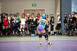 """Derby name - """"Isabelle Ringer"""" of the San Diego Derby Dolls displays her derby name while coaching a group of skaters."""