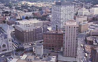 Denver - Downtown Denver cityscape, 1964. Includes Denver's oldest church (Trinity United Methodist), first building of the Mile High Center complex, Lincoln Center, old brownstone part of the Brown Palace Hotel, and Cosmopolitan Hotel – since demolished.