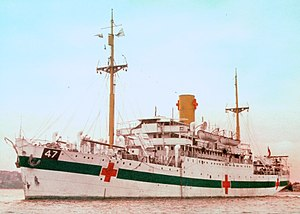 "A single-funnelled merchant ship at rest. The ship is painted white, with a dark green horizontal band along the hull, interspersed by three red crosses. The number ""47"" is painted near the bow, in a black box above the green line."