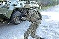 A Ukrainian Soldier dashes across a road near BTR-80.jpg