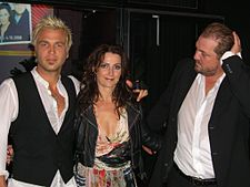 A man with blonde hair wearing a white T-shirt, a smiling woman with brown hair wearing a dress and another man wearing a suit and touching his head.