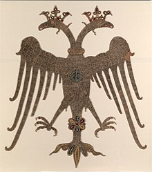 Photograph of a golden embroidered-double-headed eagle on an off-white background, with crowned heads and spread wings and legs, carrying a round medallion with Greek inscriptions on its breast.