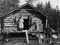 Anton Norsas stabbur til klær, bygget 1914. En mann og en kvinne står foran stabburet. Abraure 1948 - Norsk folkemuseum - NF.05116-046.jpg