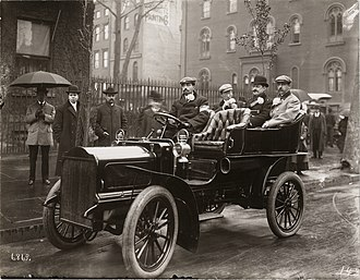 American Automobile Association - Augustus Post, an original founder of the American Automobile Association, driving his 1905 White Steamer in New York City parade. In background is Mark Twain's house, Passengers include Stanton Sickles at left and a Tammany Hall politician at right.