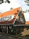 foto van Blok met 8 keukenwoningen, zo genoemd vanwege destijds nieuwe plaatsing van keuken aan de voorzijde, aan de zijkant een houten topgevel, bouwstijl Amsterdamse School, samen met de poortgebouw langs de Purmerweg centraal deel van Tuindorp Nieuwendam