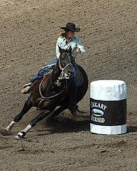 Женщина на коне резко разворачивается вокруг белой бочки.