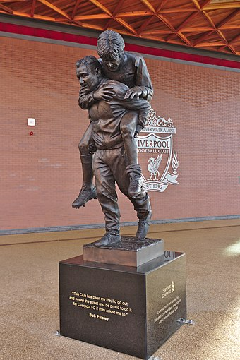 Statue of Paisley carrying an injured future Liverpool captain Emlyn Hughes, unveiled in 2020 Bob Paisley statue, Anfield 2.jpg